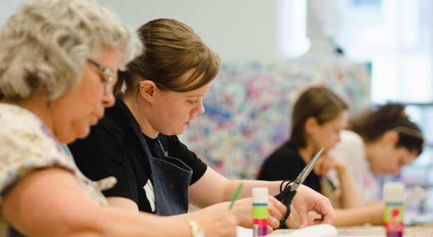 Art Hive participants work with scissors and paint at a work bench.