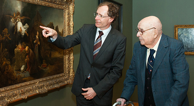 Alfred and curator discussing painting