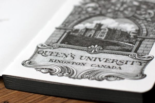 Open notebook with Queen's University illustration
