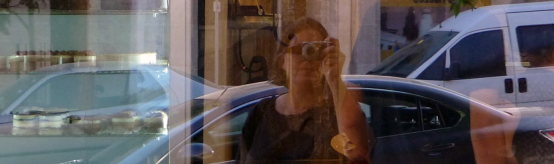 Woman taking a photograph and reflection in a window