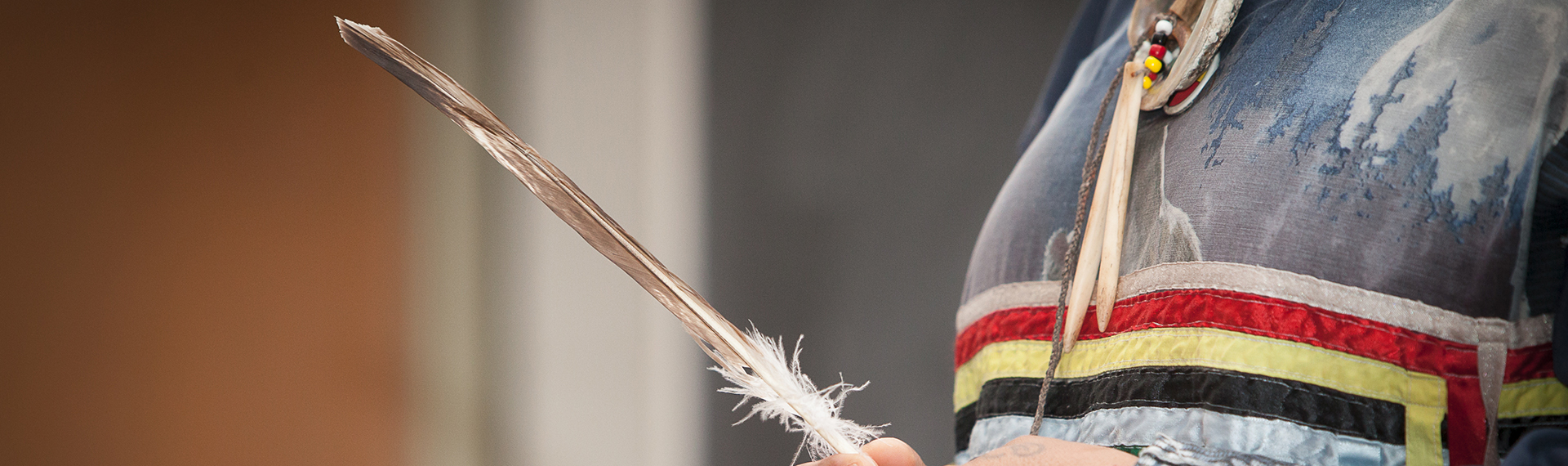 indigenous person holding a feather