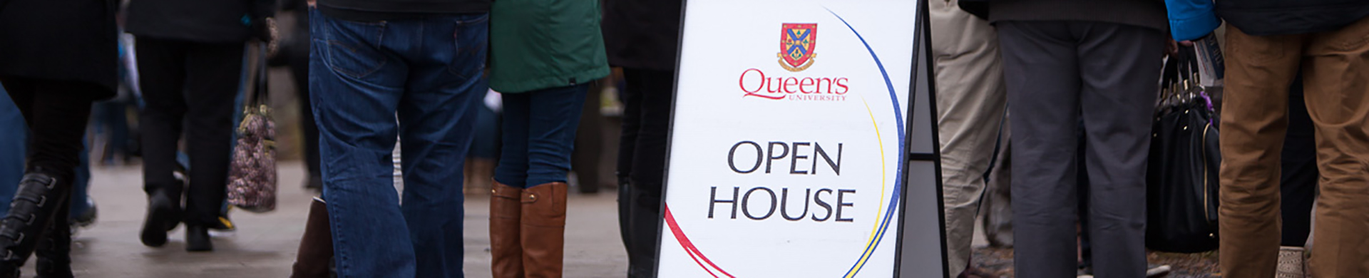 Queen's open house sign with people's feet around it