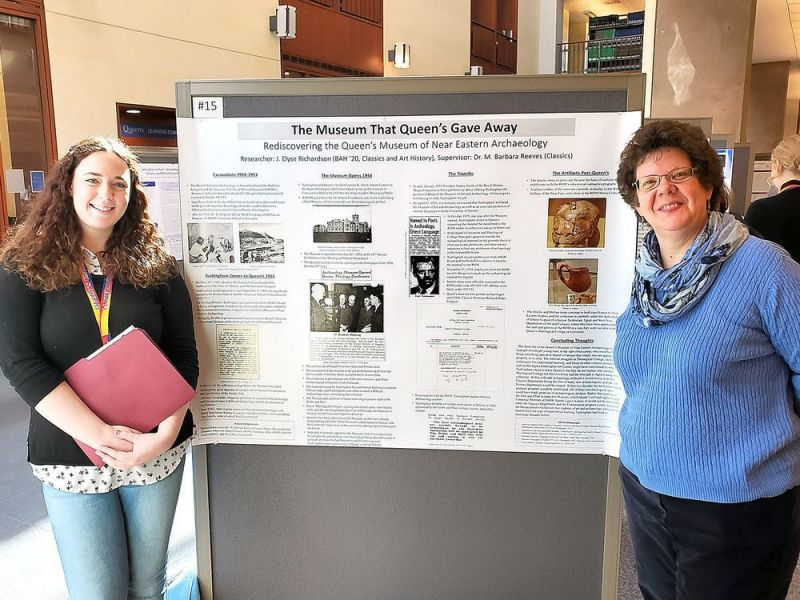 Elyse Richardson, left, a fourth-year student of classics and art history at Queen's University, and Barbara Reeves, an associate professor and an archeologist in the classics department at Queen's with a poster highlighting a former archeological museum on the Queen's campus. (Supplied Photo)