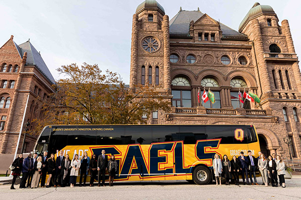 Staff and Faculty standing in front of Queen's Gaels bus at Queen's Park