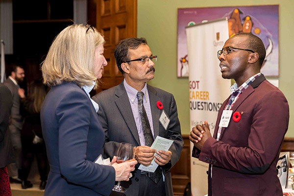 Dean of the Faculty of Arts and Science Barbara Crow and Vice-Provost and Dean of Graduate Studies Fahim Quadir speak to DDQIC alumnus Norman Musengimma (founder and CEO, Bizskills Academy).