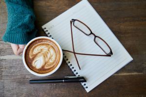 Coffee, notebook, glasses, pen and hand