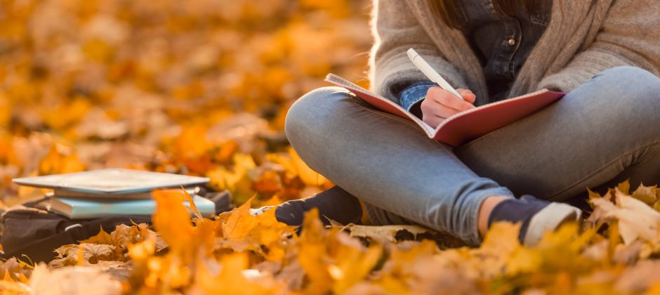 A woman studying outside in the fall