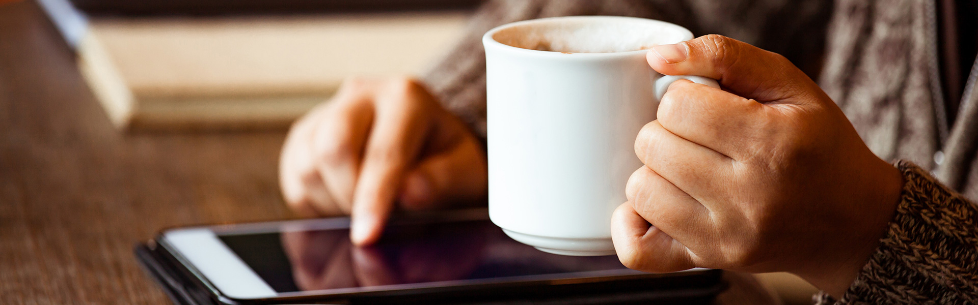 Someone's hands holding a coffee and using an ipad