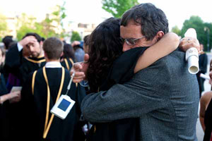 Picture of female student at Queen's convocation ceremony embracing her father outside of Grant Hall building.