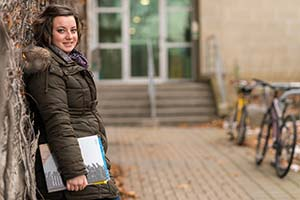 Queen's online student Erica Gough leaning against a wall with textbooks