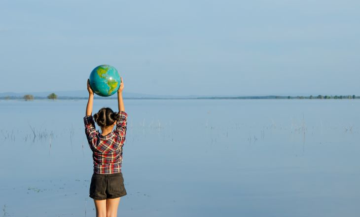 Girl holding a globe above her head, facing the water