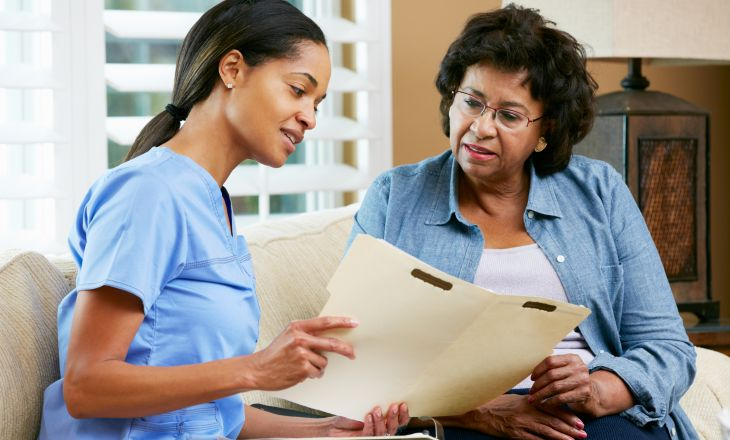 A healthcare professional sharing information in a folder with a client