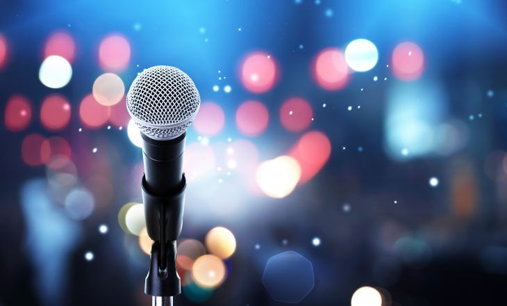Microphone with bokeh background to represent a crowd