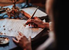 Woman writing with a fountainpen in candlelight