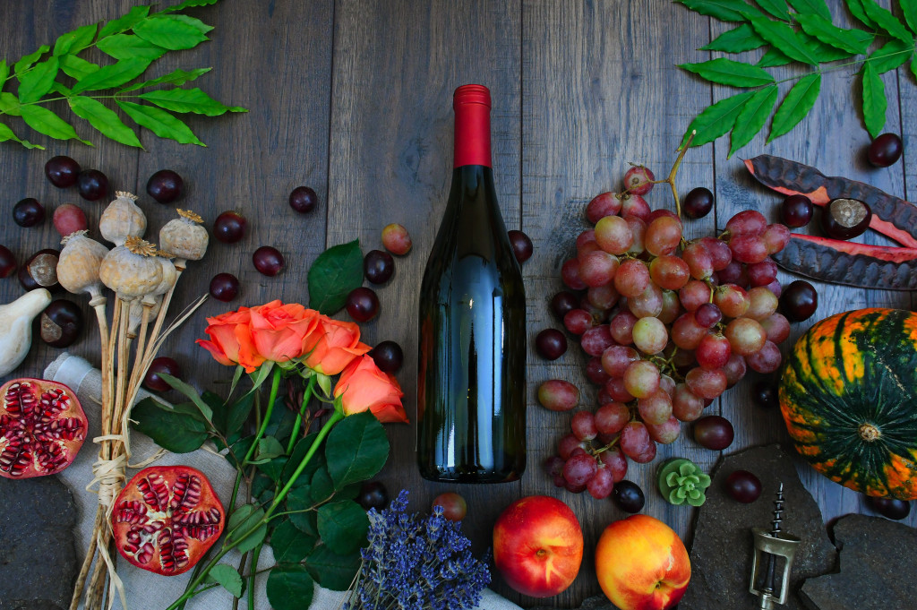 wine-bottle-beside-grapes-roses-and-several-fruits-on-brown-1407857