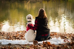 White standard poodle is in a sitting position beside owner who is in kneeling position. Both are sitting on a white blanket, facing water with trees reflecting on it.