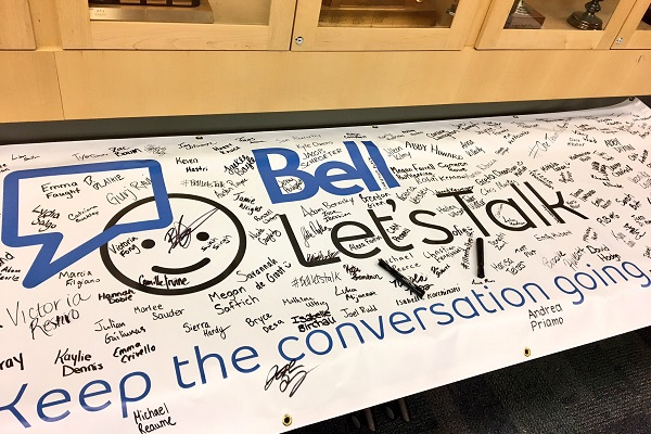 "A signed Bell Let's Talk banner with the tagline ""Keep the conversation going""."
