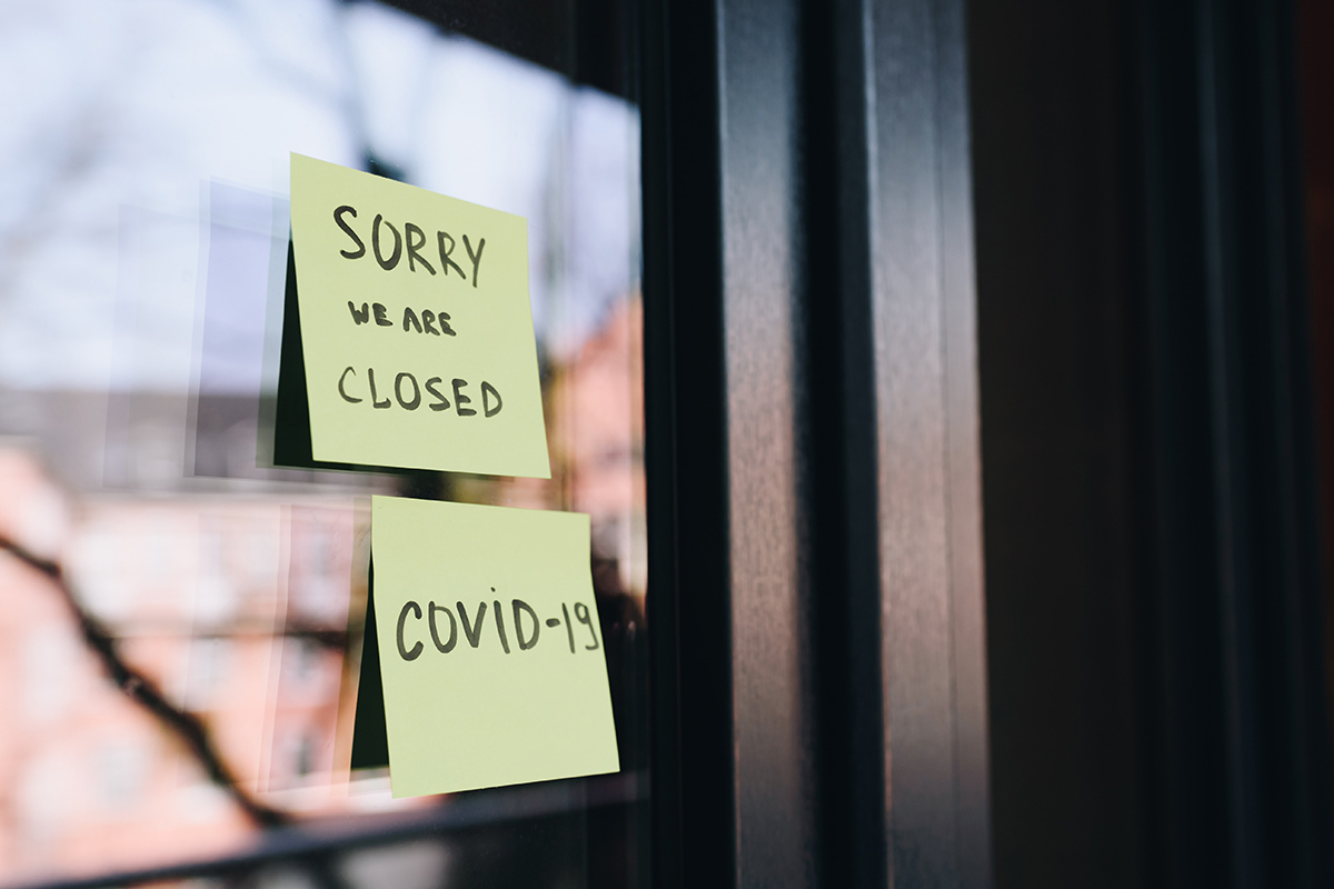 A Post-It note on glass door announces a business is closed due to COVID-19.