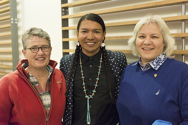 James Makokis (centre) standing with lecture series supporters M. Nancy Tatham (left) & Donna Henderson (right).