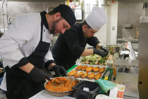 Queen's Hospitality kitchen staff preparing meals.