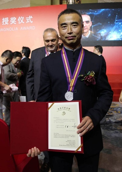 [Dr. Zhang poses with his award.]