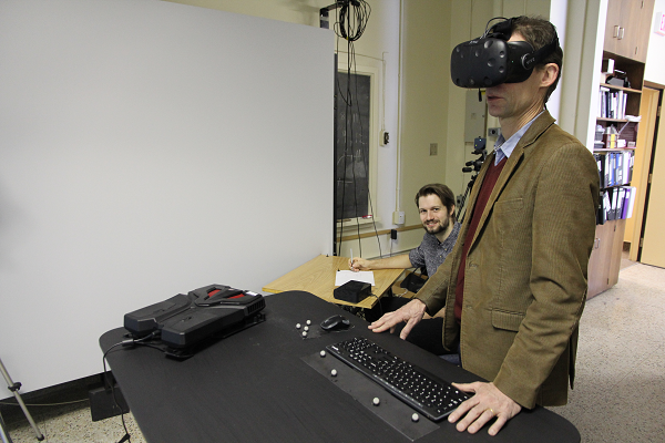 Nikolaus Troje explores virtual reality while PhD candidate Christoph Lenk monitors his progress. (University Communications)
