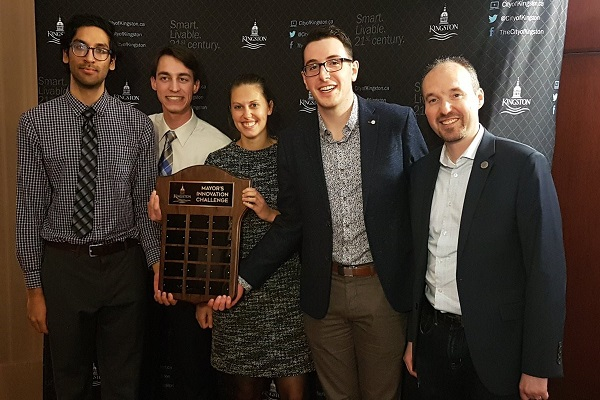 Mayor Bryan Paterson (MA'01, PhD'07) poses with Gurraj Ahluwalia, Nick Kuhl, Anna Geladi, and Mac Fitzgerald, members of a winning team from the Master of Planning program. The team pitched a winter cycling network that includes a pilot project for a two-way bike lane along Johnson Street. (Supplied Photo)