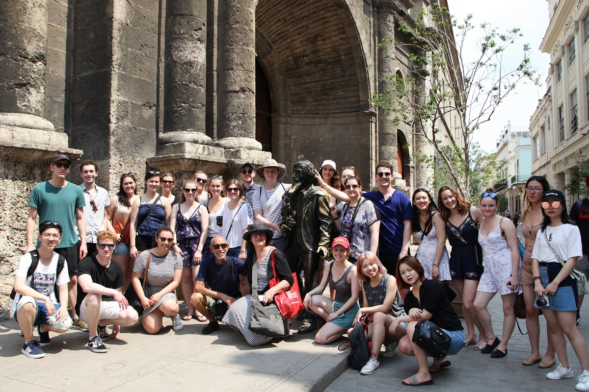 [The 2018 Cuba trip cohort pose together with a statue in Havana. (Photo: Chris Tianyu Yao)]