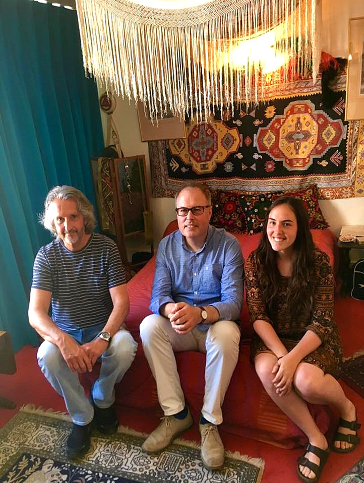 From left to right: Doug Kaye, former neighbour of guitarist legend Jimi Hendrix, Dr. Christopher Lloyd, Academic Director of the Bader International Student Centre, and Jena Hudson (ArtSci'18), USSRF fellow, sit on Jimi Hendrix's bed in his former apartment while conducting a research interview.