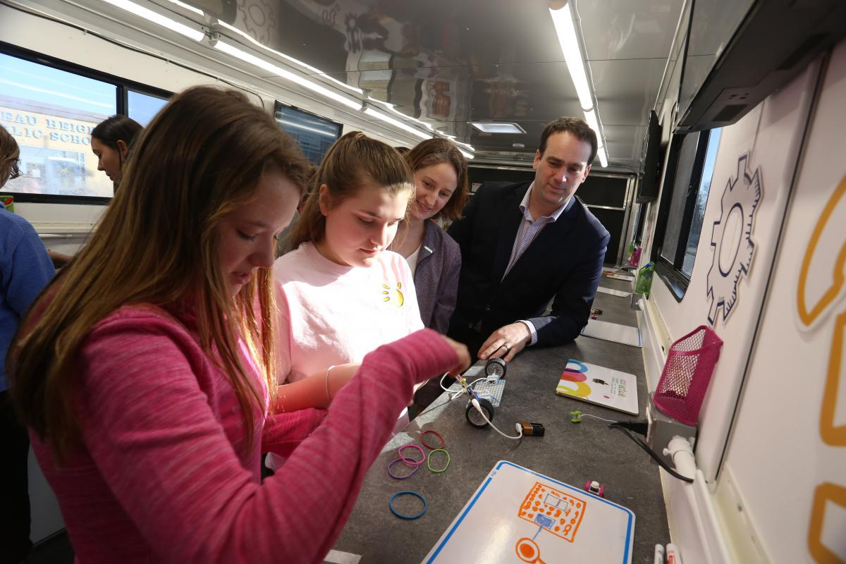 Kingston and the Islands MP Mark Gerretsen and local grade school students try their hand at some robotics experiments in the Queen's Tinker Trailer. (University Communications)