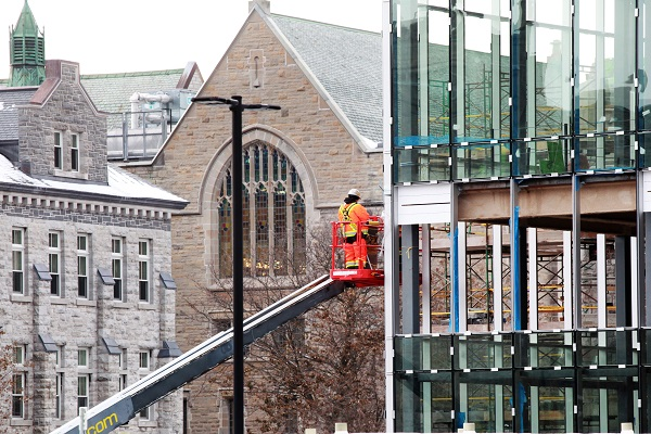 Workers continue to install glass panels on the south side of the Innovation and Wellness Centre. (Photo by Bernard Clark)