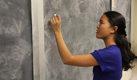 Dr. Magpantay writes on a blackboard in Jeffrey Hall. (University Communications)