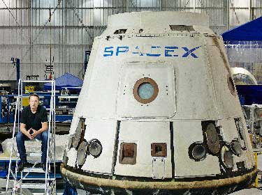 Elon Musk with a Dragon space capsule