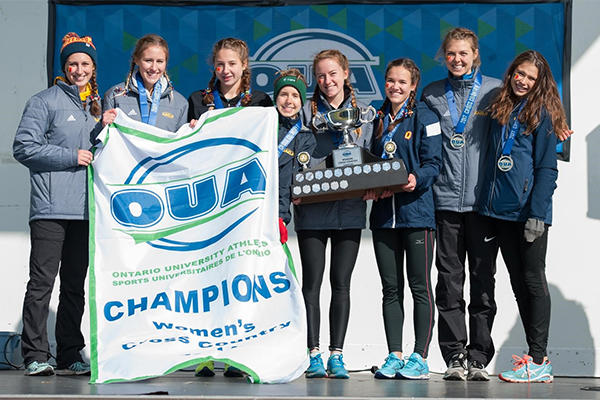 """Women's cross country team holds up OUA banner"""