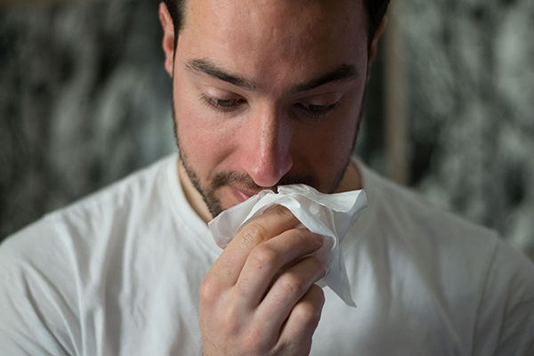 A man wipes his nose with a tissue