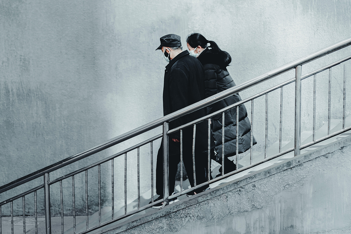 A couple wearing masks descend concrete stairs.
