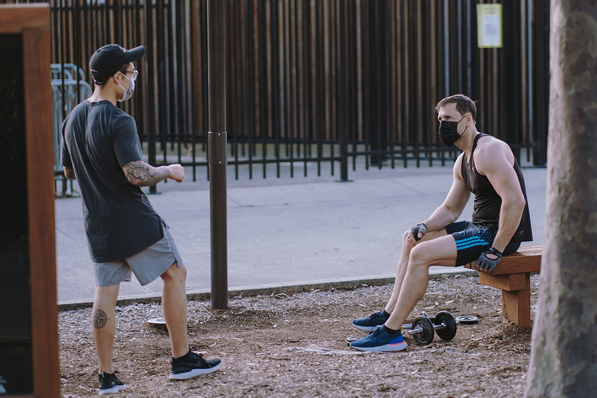 Two men wearing masks speak with each other during an outdoor workout.