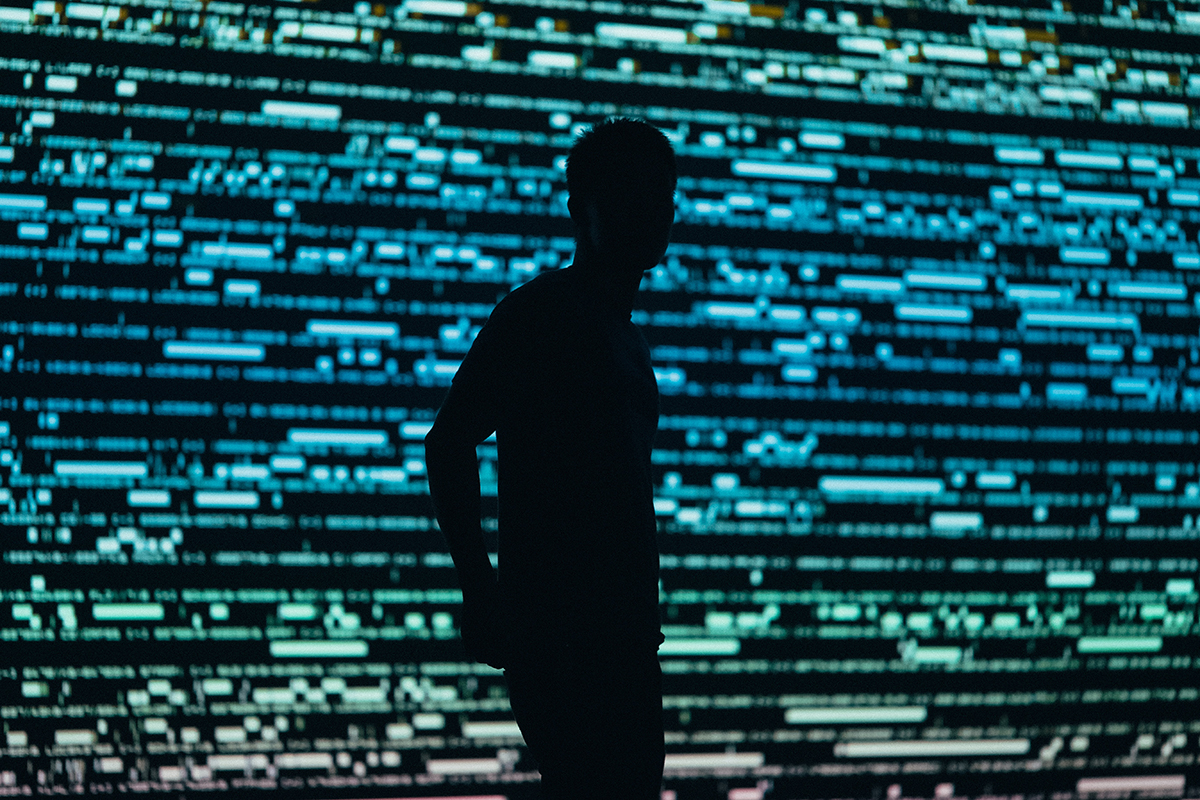 A silhouetted man stands in front of a digital display.