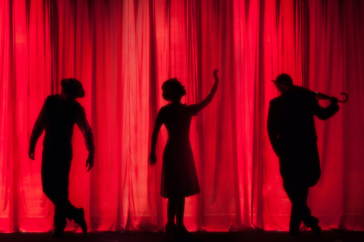 Three artists silhouetted on a theatre stage infront of a bright red curtain