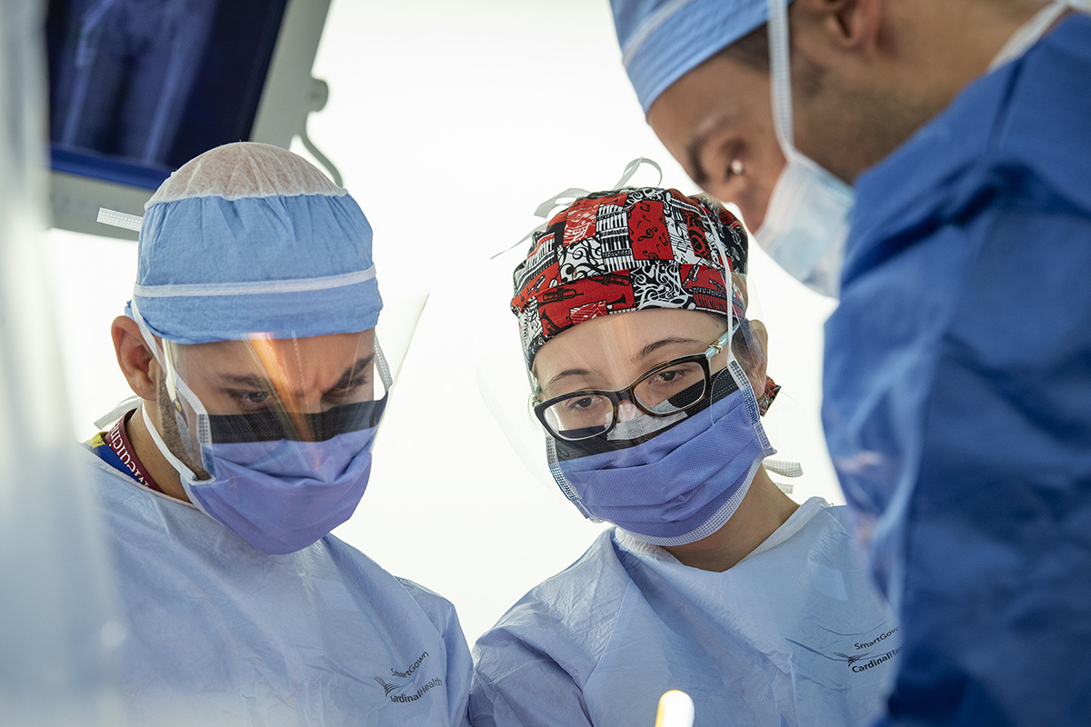 Three health care professionals are seen as they work on a medical procedure.
