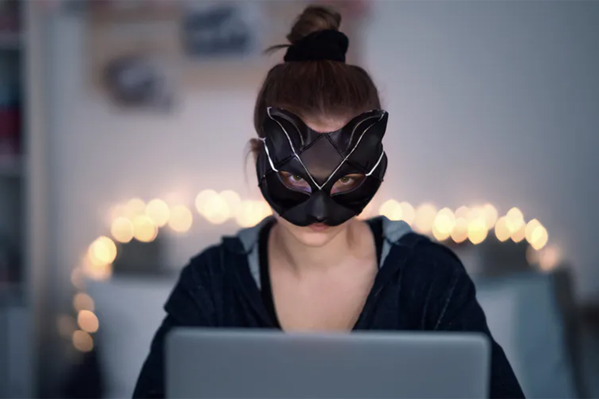 A woman wears a mask around her eyes as she looks at a computer