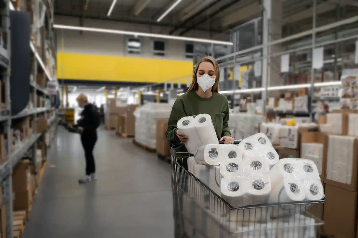A woman shopper wearing a surgical mask stocks up on toilet paper at a supermarket
