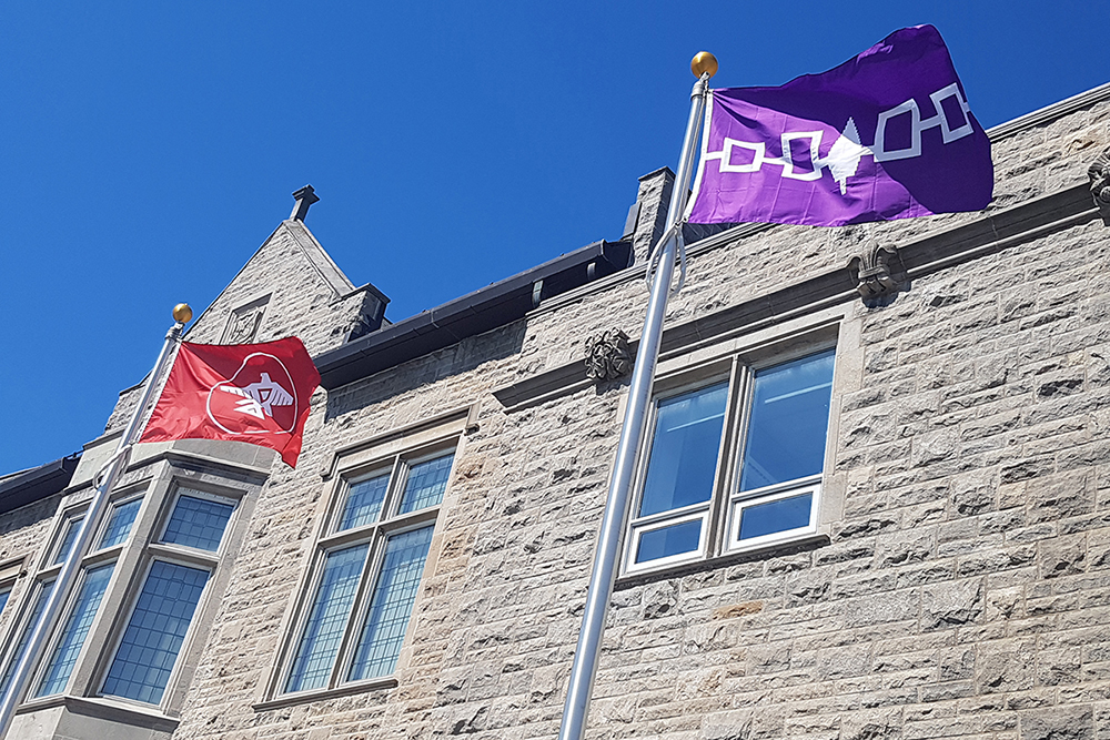 Anishinaabe and Haudenosaunee flags flying in front of Richardson Hall