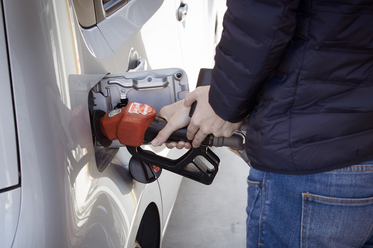 A man pumps gasoline into a silver car