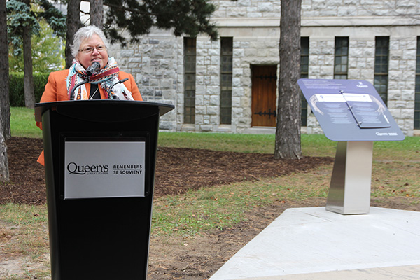 Kanonhsyonne (Jan Hill) speaks at a ceremony unveiling the Queen's Remembers Indigenous plinth, located on McGibbon Walk. (University Communications)
