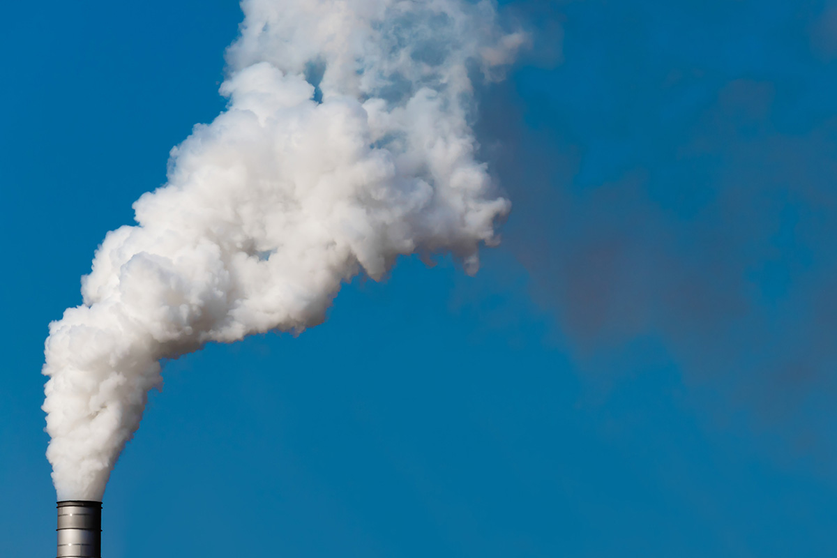 A smokestack expels steam into the air.