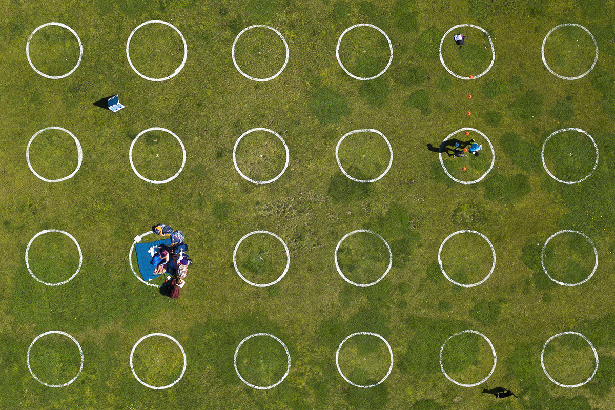People sit in circles in a park for social distancing.