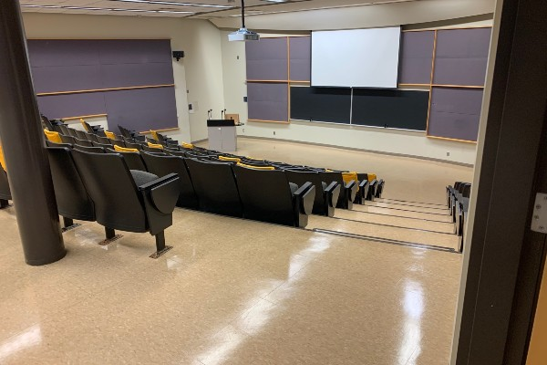 Photograph of a lecture hall with markers on seats to promote physical distancing.
