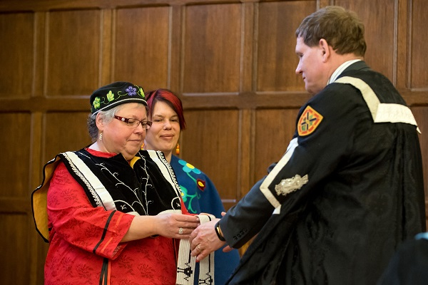 [Principal Daniel Woolf and Kanonhsyonne (Janice Hill) hold a wampum belt]
