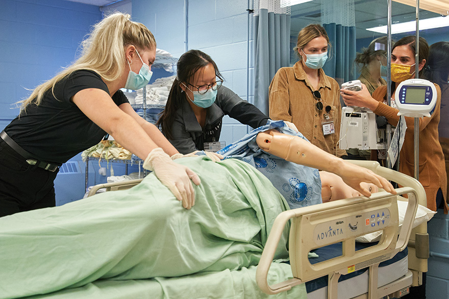 [photo of nursing students working with an instructor]